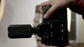 Close up da câmera profissional de DSLR que fotografa uma jovem senhora atrativa em um estúdio branco - vídeos de arquivo