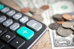 Close up da calculadora mais o botão verde com dinheiro na placa de madeira Foto de Stock