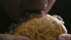 Close-up da cara do homem, mordendo fora de um hamburguer suculento delicioso filme