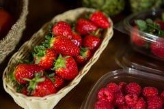Close-up da cesta de vime pequena completamente da morango na seção orgânica Foto de Stock