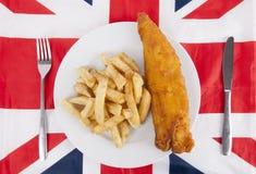 Close-up da comida lixo com a faca da forquilha e de tabela sobre a bandeira britânica Foto de Stock