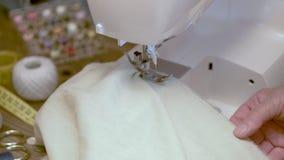 Close-up da costureira que costura a roupa na máquina de costura elétrica Movimento lento filme