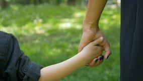 Close-up da criança que agarra e que guarda a mão da mãe vídeos de arquivo