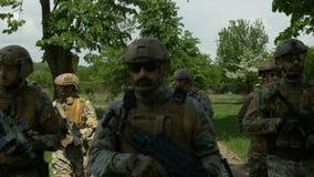 Close up da equipe militar que anda em uma formação na patrulha fora em uma área rural ao guardar suas armas video estoque