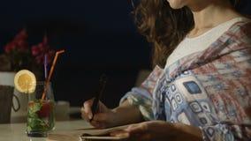 Close up da escrita bonita feliz e inspirada da mulher no diário com sorriso na cara filme