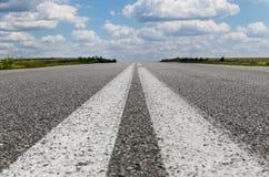 Close up da estrada asfaltada com duas linhas brancas no centro Imagem de Stock