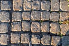 Close-up da estrada da pedra, teste padrão, fundo Luz solar lateral da noite imagens de stock royalty free