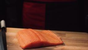 Close-up da faixa crua dos salmões na placa de madeira com faca Ideia da parte suculenta de salmões antes de cortar a preparar-se filme