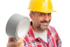 Close-up da fita adesiva guardado pelo construtor foto de stock