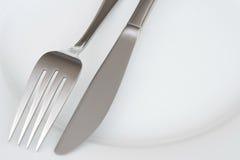 Close up da forquilha e faca em uma placa Foto de Stock Royalty Free