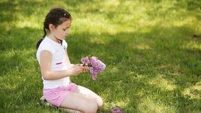 Close-up da grinalda feliz da trança da menina das flores no prado video estoque
