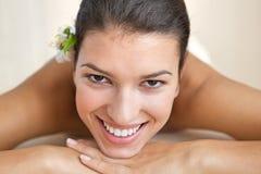 Close-up da jovem mulher alegre que relaxa na tabela da massagem Foto de Stock Royalty Free