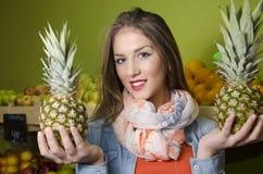 Close up da jovem mulher bonita, guardando abacaxis Imagens de Stock Royalty Free