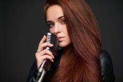 Close up da jovem mulher com microfone retro imagem de stock