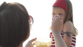 Close-up da jovem mulher que alimenta a filha pequena na praia video estoque