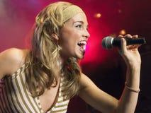 Close up da jovem mulher que canta no microfone Foto de Stock Royalty Free