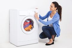 Close up da jovem mulher que pressiona o botão da máquina de lavar fotografia de stock royalty free