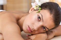 Close-up da jovem mulher que relaxa na tabela da massagem Imagem de Stock