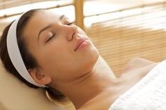Close-up da jovem mulher que relaxa na tabela da massagem, olhos fechados Fotos de Stock Royalty Free