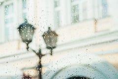 Close-up da lâmpada de rua Vista da janela com gotas da chuva, bokeh borrado da rua, tempo do outono, estações seletivo Fotos de Stock