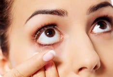 Close up da lente de contato vestindo da jovem mulher fotografia de stock royalty free