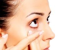 Close up da lente de contato vestindo da jovem mulher imagem de stock
