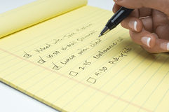 Close up da lista da escrita da mão da fêmea de tarefas fazer Imagens de Stock