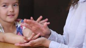 Close up da mãe e da filha que mantêm as mãos afetuosas com espaço da cópia na tabela em um café video estoque