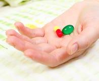 Close up da mão da mulher que prende dois comprimidos Imagem de Stock