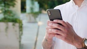 Close-up da mão de homem de jovens que guarda usando um telefone video estoque