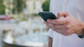Close-up da mão de homem de jovens que guarda usando um telefone vídeos de arquivo