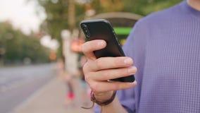 Close-up da mão de homem de jovens que guarda usando um telefone filme