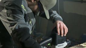 Close-up da mão de um carpinteiro que trabalha com um cortador elétrico manual em uma oficina da casa Peças de madeira de termina vídeos de arquivo