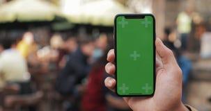 Close up da mão de um homem que guarda um celular com uma tela verde vertical nas ruas O bonde do turista vai no filme