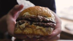 Close-up da mão de um homem que guarda um hamburguer suculento de dar água na boca grande vídeos de arquivo