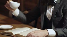 Close-up da mão de um homem que guarda um livro de papel aberto, girando as páginas com seus dedos e chá das bebidas M?o do `s do vídeos de arquivo