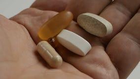 Close-up da mão de um homem que guarda muitos comprimidos em sua palma video estoque