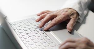 Close-up da mão de uma mulher idosa com enrugamentos que datilografa em um teclado filme