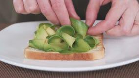 Close up da mão de uma mulher que esteja preparando um sanduíche com abacate e beterrabas para o café da manhã, apresentação filme