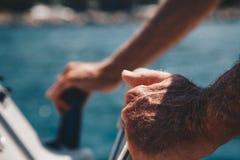 Close-up da mão do capitão superior no volante do barco de motor fotografia de stock