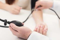 Close up da mão do doutor usando o tonometer imagens de stock