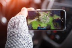 Close-up da mão do homem que joga jogos de vídeo no smartphone imagem de stock