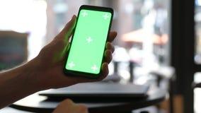 Close-up da mão do homem usando o telefone celular com a tela verde no restaurante filme