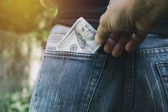 Close-up da mão do ladrão que rouba o dinheiro de uma mulher Thi imagens de stock royalty free