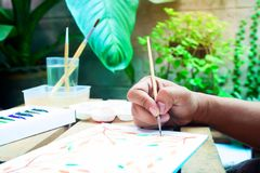 Close up da mão do ` s do homem com pintura da escova no bloco de notas Criação p imagens de stock