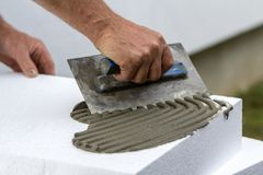 Close-up da mão do trabalhador com a pá de pedreiro que aplica a colagem na folha rígida branca da espuma de poliuretano para a i imagem de stock royalty free