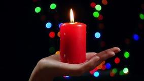 Close-up da mão fêmea com uma vela vermelha grande no fundo do bokeh Vela ardente em um fundo preto Religião video estoque