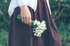 Close up da mão fêmea que guarda um grupo dos snowdrops imagem de stock royalty free