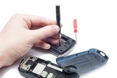 Close-up da mão humana que repara o telefone celular com chave de fenda Fotografia de Stock Royalty Free
