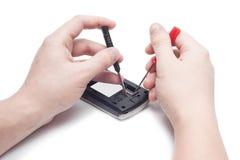 Close-up da mão humana que repara o telefone celular com chave de fenda Foto de Stock